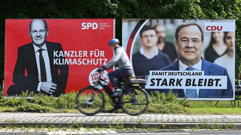 Ein Radfahrer fährt am Dienstag an großen Wahlplakaten mit den Spitzenkandidaten Olaf Scholz (SPD, l) und Armin Laschet (CDU) in Frankfurt vorbei.