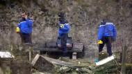 Französische Polizeibeamte suchen nach Spuren in den umgestürzten Grabstellen des geschändeten jüdischen Friedhofs von Sarre-Union.