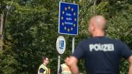 Bundespolizisten stehen am 16. September 2015 an einem Grenzschild der Bundesrepublik Deutschland an der deutsch-österreichischen Grenze zwischen Salzburg und Freilassing (Bayern).