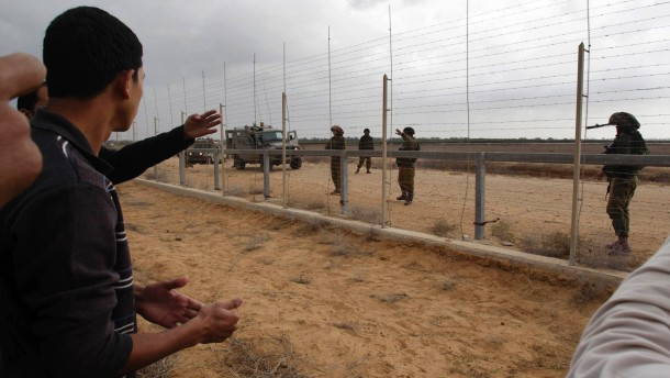 Palestinian looks at Israeli soldiers as they stand guard behind fence between Israel and southern Gaza Strip