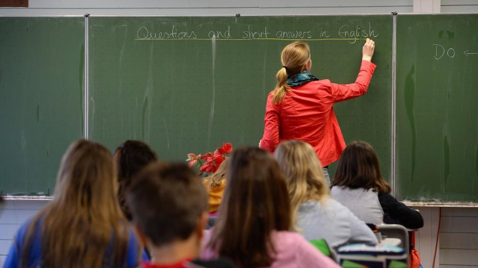 Eine Studienrätin schreibt in einem Klassenzimmer im Theodor-Heuss-Gymnasium in Esslingen (Baden-Württemberg) während des Englischunterrichts der Klasse 5e an die Tafel (Archivbild).