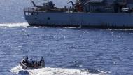 Vor der libyschen Küste: Rettungsboot mit Flüchtlingen vor einem Militärschiff der Operation Sophia im März