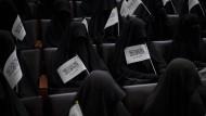 In schwarze Burkas gehüllte Frauen sitzen in einem Hörsaal der Universität in Kabul und halten Taliban-Fahnen in den Händen.