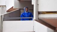 Ein BKA-Beamter in Schutzkleidung steht am 15. Juni in dem Wohnkomplex Osloerstr. 3 in Köln-Chorweiler auf einem Balkon.