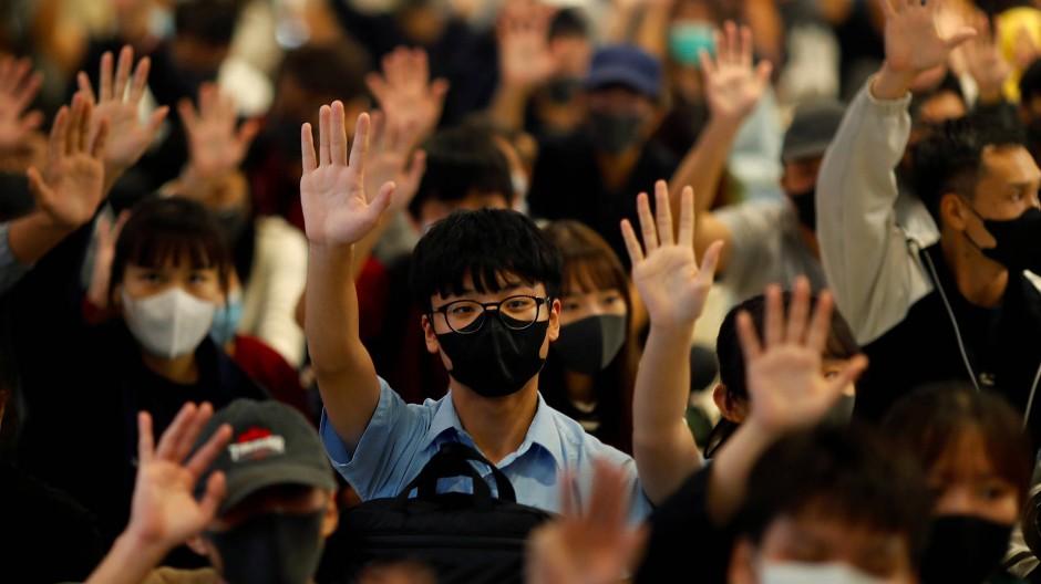 Demonstranten halten während einer Kundgebung in Hongkong ihre Hände empor.
