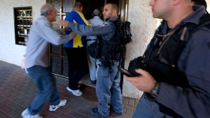 Israelis police instrut people to enter a shelter in Ashkelon dur
