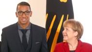 Weltmeister Deutschland: Fußball-Nationalspieler Jerome Boateng präsentiert das Silberne Lorbeerblatt neben Bundeskanzlerin Angela Merkel (CDU) am 10. November 2014 im Schloss Bellevue in Berlin.
