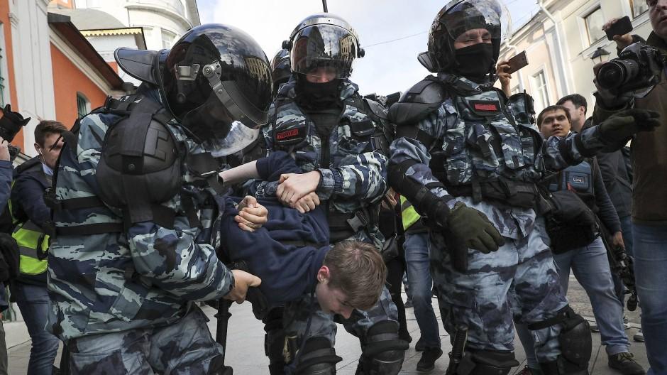 Russische Polizisten führen einen Demonstranten in Moskau ab.