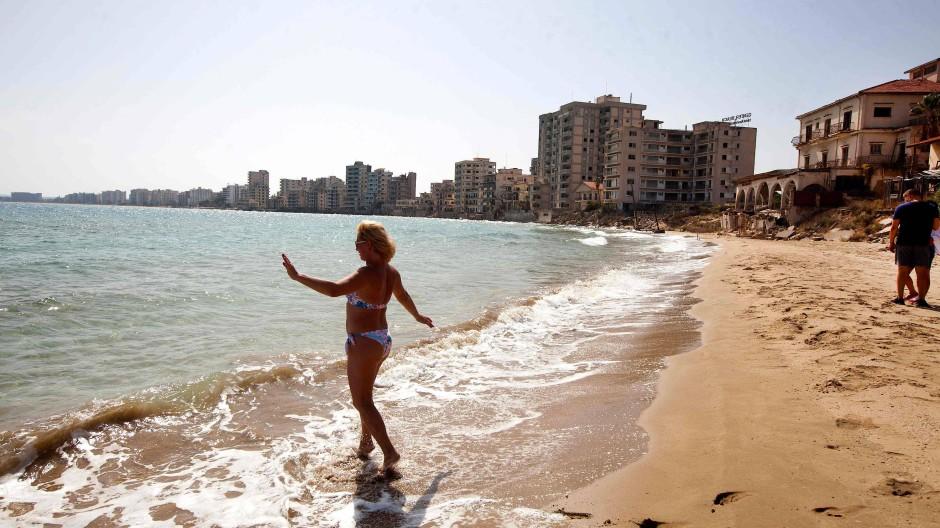 Eine Frau geht vor der Silhouette verlassener Hotels erstmals seit Jahrzehnten im Oktober am Strand von Varoscha baden.