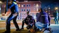 Ein Mann wird nach einer Konfrontation in Rotterdam von Polizisten am Boden festgehalten.