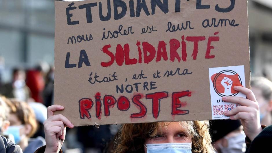 Eine Studentin hält während einer Demonstration in Paris am 20. Januar ein Plakat hoch. Es trägt die Aufschrift: Ihre Waffe ist es, uns zu isolieren, unsere Antwort  ist Solidarität.