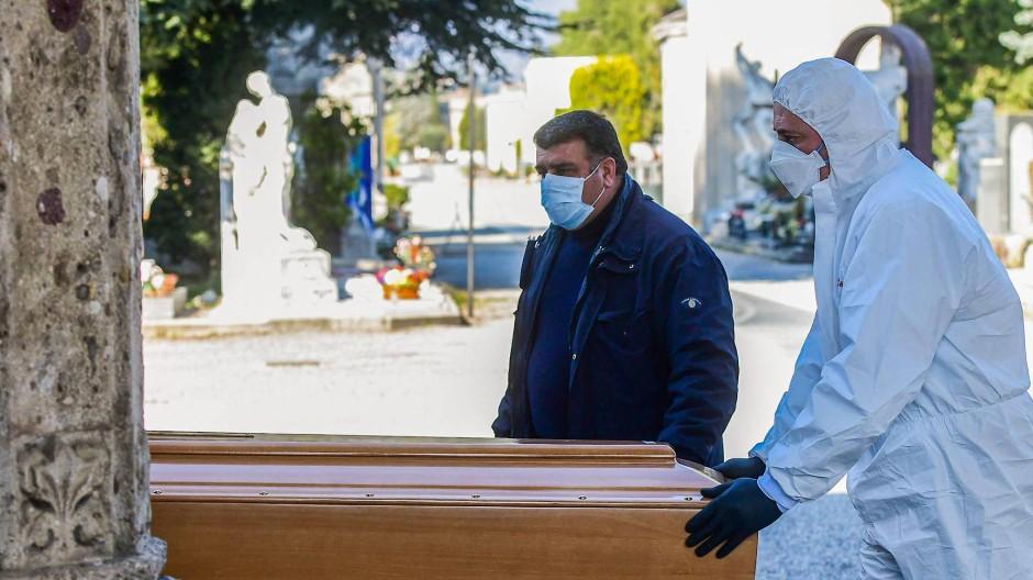Bestatter schieben einen Sarg auf dem Hauptfriedhof von Bergamo.