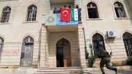 Von der Türkei unterstützte syrische Kämpfer halten eine türkische und eine syrische Flagge vom Ratsgebäude im kurdischen Afrin.