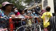Angehörige und Freunde von Häftlingen warten am Samstag vor einem Gefängnis in Yangon.