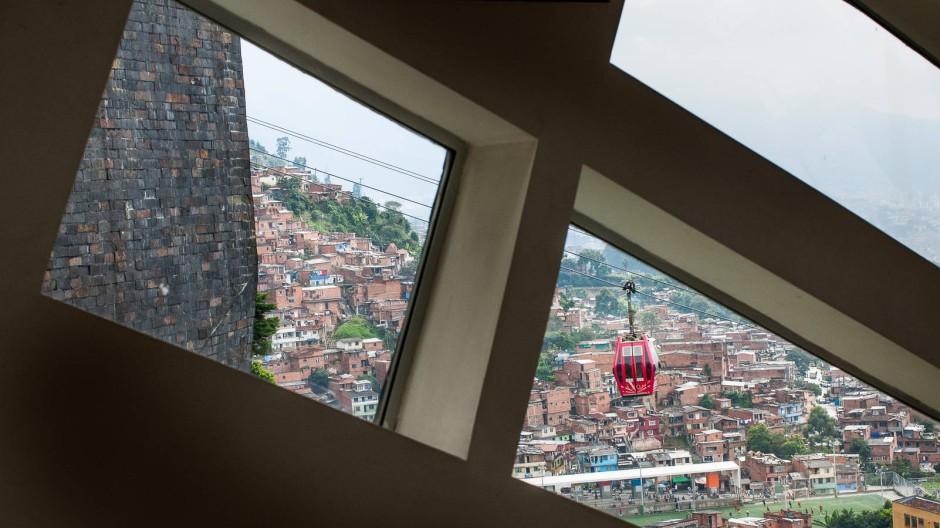 """Ewiger Frühling: Blick durch die Fenster der """"Biblioteca Espana"""" auf eine Gondel des """"Metrocable"""" in Medellin"""