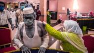 Eine Helferin impft einen Mann in Bangladesch, Barishal. Nachdem die Menschen in Bangladesch vier Monate auf eine zweite Corona-Impfung warten mussten, hat das Land im Rahmen der internationalen Hilfsinitiative Covax Impfstoffe von Japan erhalten.