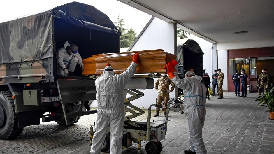 Särge von Covid-19-Opfern aus der Gegend von Bergamo werden im März 2020 von Arbeitern am Friedhof von Cinisello Balsamo ausgeladen.