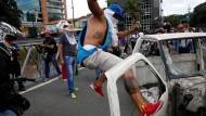 Ein vermummter Demonstrant versucht während der Proteste in Venezuelas Hauptstadt Caracas die Tür eines bereits zerstörten Autos abzutreten.