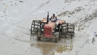 Bewässerung per Monsun: Mit einfachsten Mitteln bestellen Indiens Bauern ihre Felder – so wie dieser Mann im indischen Telangana.