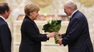 Blumen bei der Ankunft: Weißrusslands Präsident Lukaschenka empfängt Bundeskanzlerin Angela Merkel