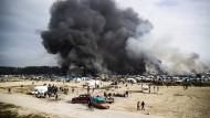 Schwarze Rauchwolken über dem Flüchtlingslager von Calais, das geräumt wird.