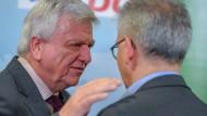 Hessens Ministerpräsident Volker Bouffier (CDU, links) und sein bisheriger Stellvertreter Tarek Al-Wazir (Bündnis 90/Die Grünen) unterhalten sich nach einem Pressestatement zu den Koalitionsverhandlungen von CDU und Grünen miteinander.