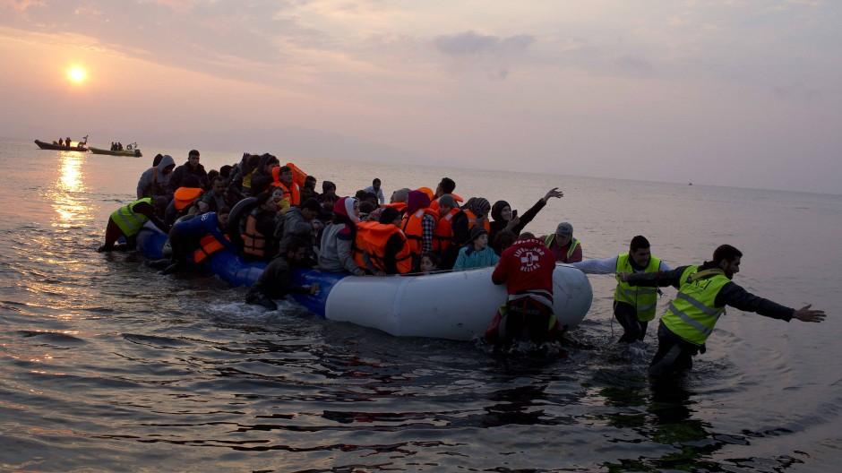 Freiwillige helfen einem Flüchtlingsboot, das an der Küster der griechischen Insel Lesbos ankommt.