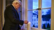 Bundespräsident Frank-Walter Steinmeier entzündet am Mittwoch eine Kerze in einem Fenster von Schloss Belvue