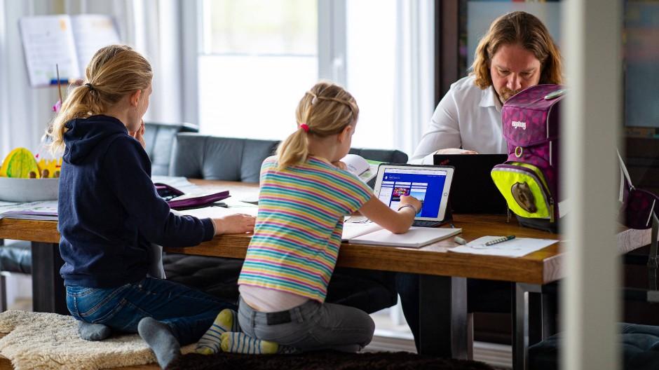 Distanzunterricht: Zwei Schwestern machen ihre Hausaufgaben und werden dabei von ihrem Vater unterstützt. (Symbolbild)