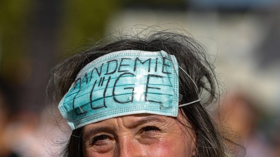"""Maskenpflicht anders gedacht: Eine Demo-Teilnehmerin in Berlin trägt ihre Maske mit der Aufschrift """"Pandemie Lüge"""" auf der Stirn."""
