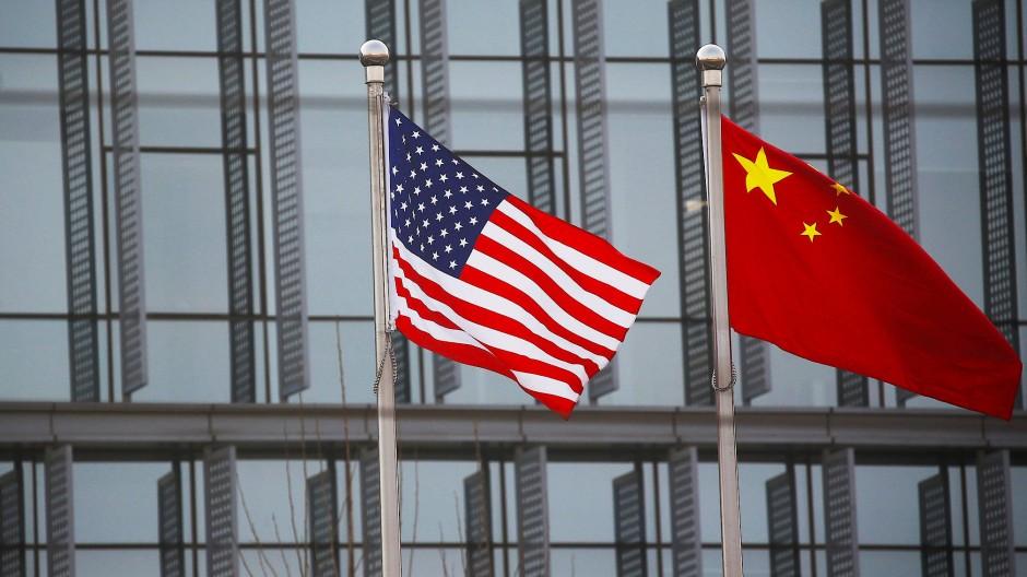 Eine amerikanische und eine chinesische Flagge vor dem Sitz eines amerikanischen Unternehmens in Peking