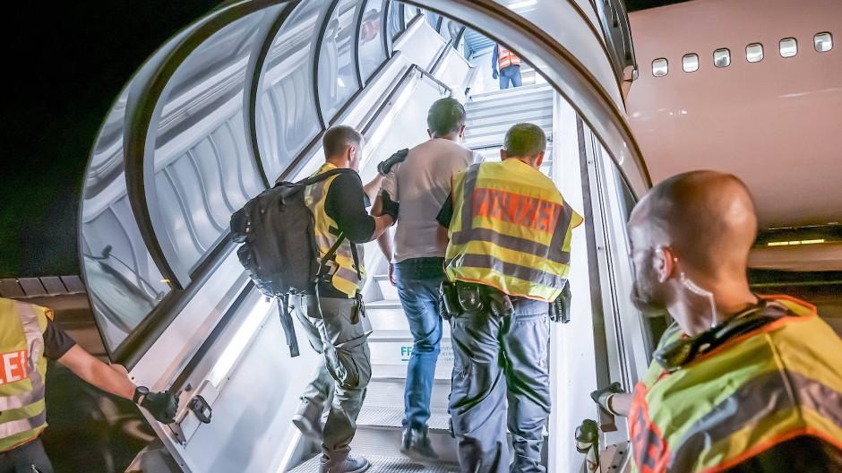 Zwei Polizisten geleiten im Juli einen Afghanen in ein Charterflugzeug auf dem Flughafen Leipzig (Symbolbild)
