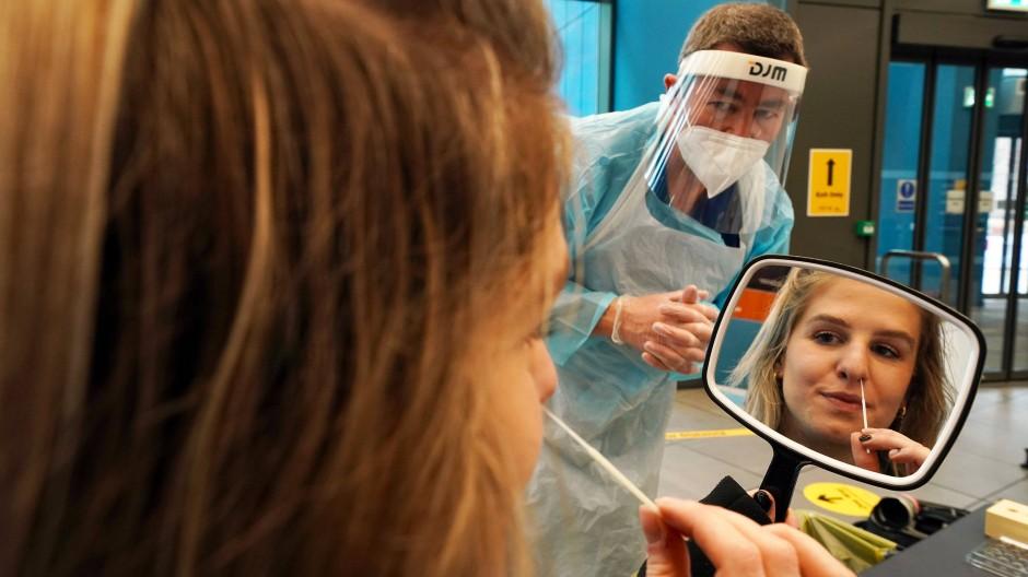 Eine Studentin an der Universität Newcastle wird von einem Gesundheitsspezialisten beobachtet, wie sie sich selbst einen Abstrich für einen Coronatest entnimmt.