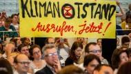 Besucher halten im Juni während der Rede von Kanzlerin Merkel bei der Jahreskonferenz des Rates für Nachhaltige Entwicklung in Berlin ein Transparent in die Höhe