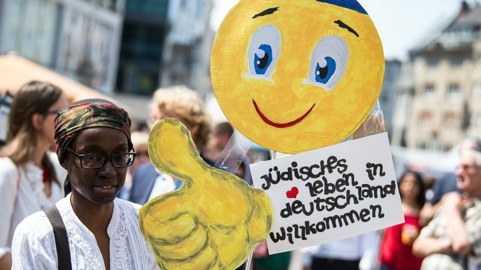 """Eine junge Frau trägt im Juli 2018 auf dem Bonner Marktplatz bei einer Demonstration gegen Antisemitismus ein Schild mit der Aufschrift """"Jüdisches Leben in Deutschland willkommen""""."""