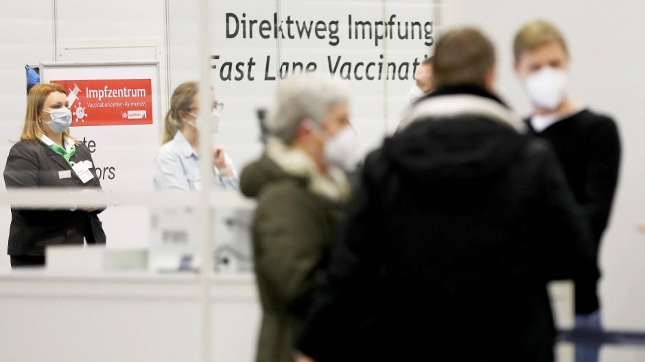 Menschen warten Anfang Februar in einem Impfzentrum in Köln an einem Schalter.