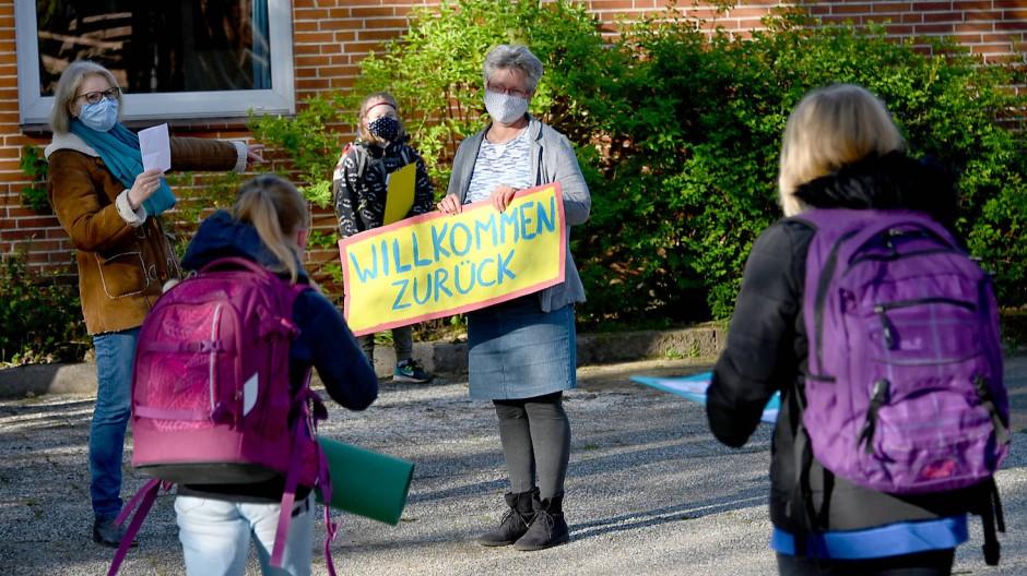 """Mit einem Schild """"Willkommen zurück"""" begrüßt eine Lehrerin im Mai 2020 die Viertklässler einer Grundschule in Aukrug in Schleswig-Holstein. (Archivbild)"""