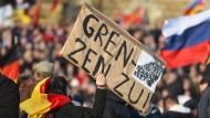 Ein Pegida-Anhänger hält eine Pappe mit der Aufschrift «Grenzen zu!» am 06.02.2016 während einer Veranstaltung am Königsufer in Dresden (Sachsen).