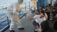 """Eine Soldatin der Fregatte """"Schleswig-Holstein"""" verteilt Decken an Flüchtlinge"""