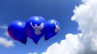 Luftballons mit dem Symbol einer Friedenstaube