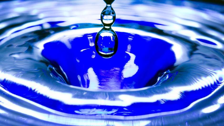 Ein Wassertropfen fällt in eine blaue Wasserschüssel.