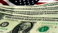 US-amerikanische Dollarnoten vor einer USA-Fahne