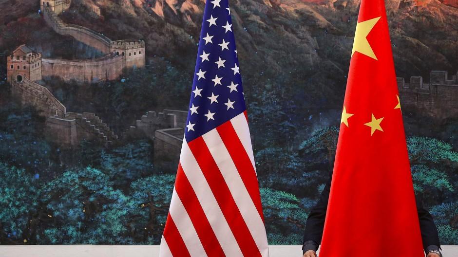 Am 5. Februar 2012 richtet ein chinesischer Beamter die Flaggen von China und den Vereinigten Staaten vor dem Besuch der damaligen US-Außenministerin Clinton.