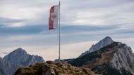 Die österreichische Flagge am 8. Oktober 2014 in Tirol vor dem Alpenpanorama