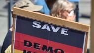 """Demonstranten halten am 04.06.2015 in München bei einer Demonstration gegen den G7-Gipfel ein Schild mit der Aufschrift """"Save Demokratie""""."""