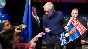 Republican presidential candidate Ron Paul signs a poster for a supporter during a rally in Henderson