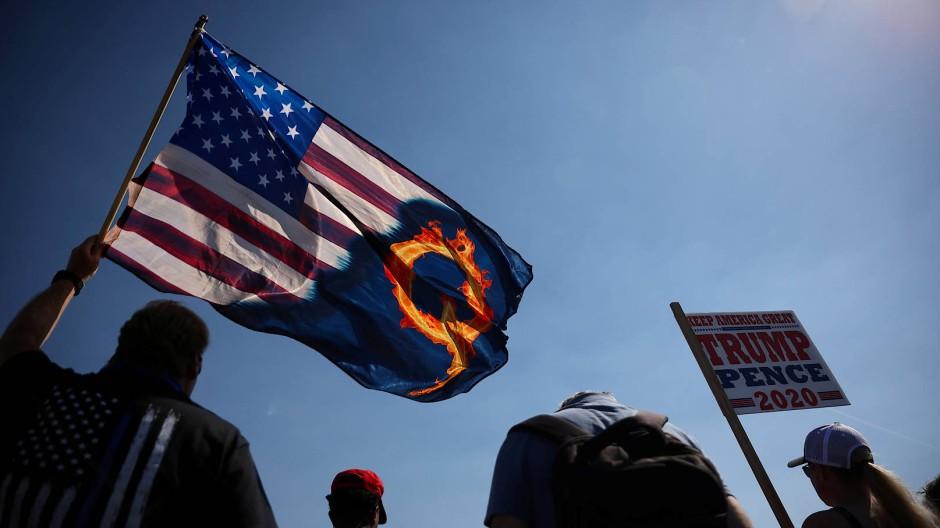"""Bei einer Demonstration für den ehemaligen Präsidenten halten Trump-Unterstützer auch eine""""QAnon""""-Flagge hoch."""