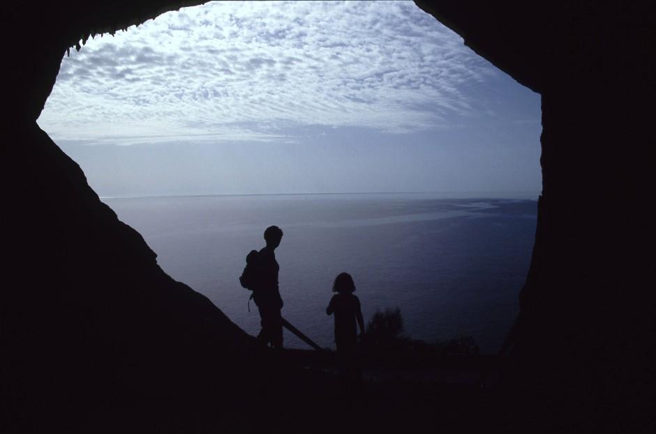 Sillouetten vor dem Höhlenausgang von Arta mit Blick auf das Meer.