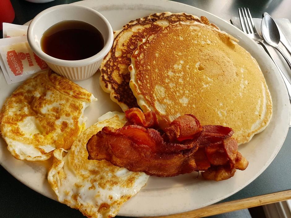 Holzfällerkost, kalorienreich: Klassisches Frühstück mit Pancakes, Schinken, Ei – und Ahornsirup.