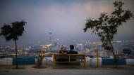 Die Lichter über Teheran glitzern wie ein Versprechen für die Zukunft: Ein junges Pärchen sitzt auf einer Bank in Bam-e Teheran, hoch über der Stadt